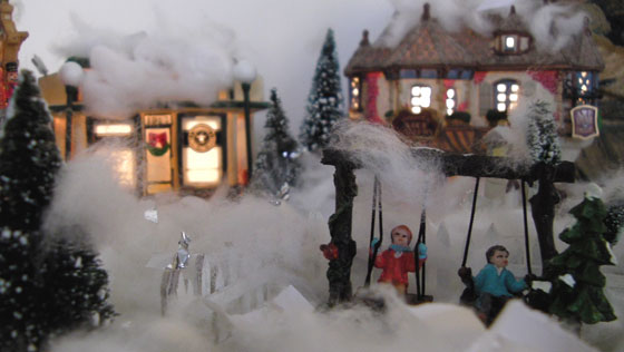 A shot of the Christmas village my son built - Street view of kids on a swing.